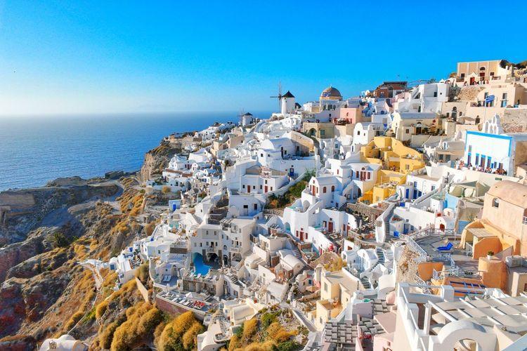 Houses By Sea Against Clear Blue Sky At Santorini