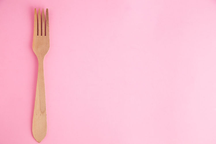 Directly above shot of wooden fork over pink background