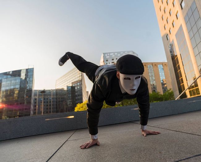 Man Wearing Mask Doing Handstand In City Against Clear Sky