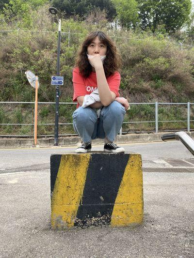 Full length of girl sitting on road