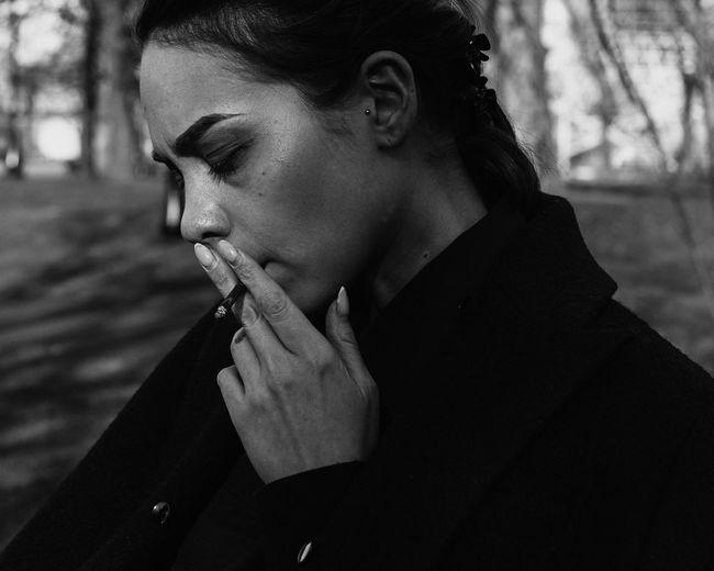 Woman looking away while smoking cigarette