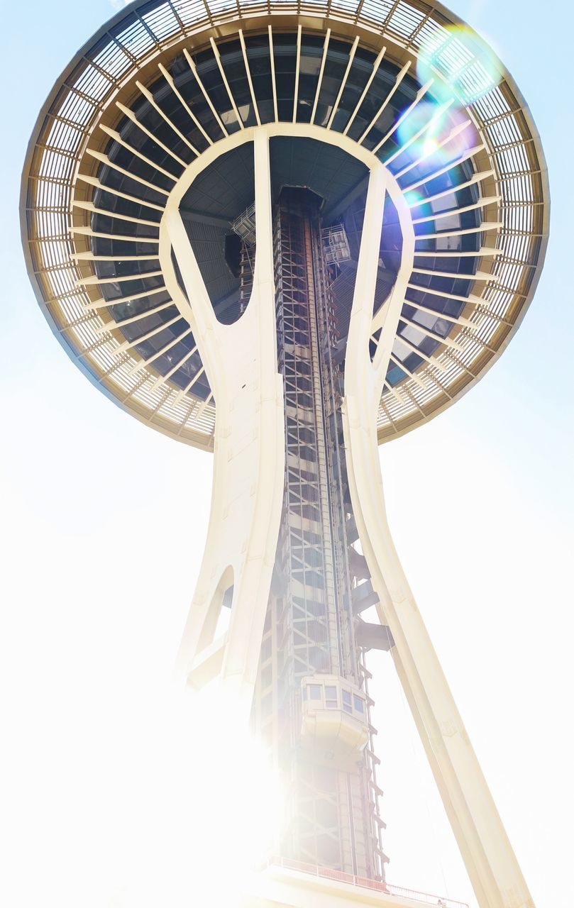 low angle view, sky, architecture, built structure, amusement park, nature, arts culture and entertainment, clear sky, amusement park ride, day, no people, sunlight, metal, outdoors, fairground, fun, ferris wheel, lens flare, tall - high, circle