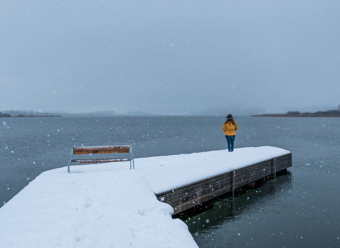 Rear view of woman standing at lake against sky during snowfall