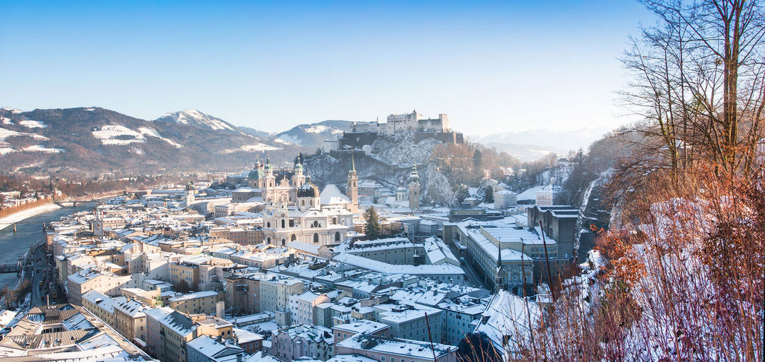 Snow covered townscape by river against clear sky