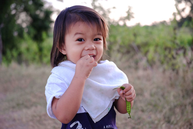 Portrait of cute girl eating bean while standing outdoors