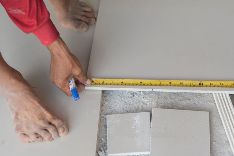 Low section of worker measuring tile