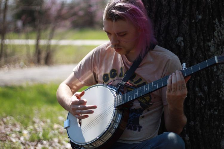 Music Plucking An Instrument Playing Musical Instrument One Person Musician Leisure Activity Real People Banjo Outdoors Tree Blurred Background Banjo Player Purple Hair Purple Jeans Sitting Sitting Outside Southern Illinois  Carbondale Relaxing Relax Shade Sun Midday