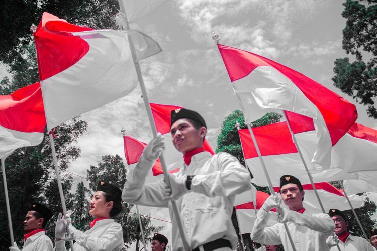 Group of people holding flag in traditional clothing