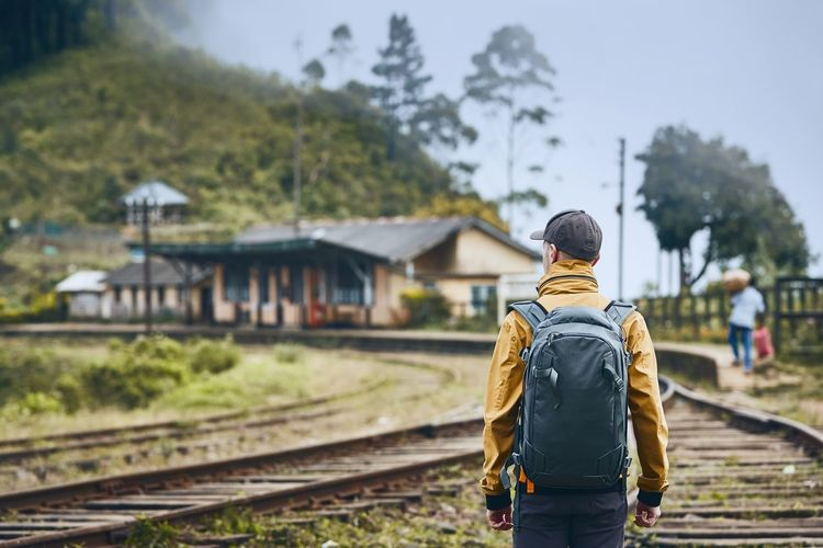 Rear view of man standing with backpack on railroad track