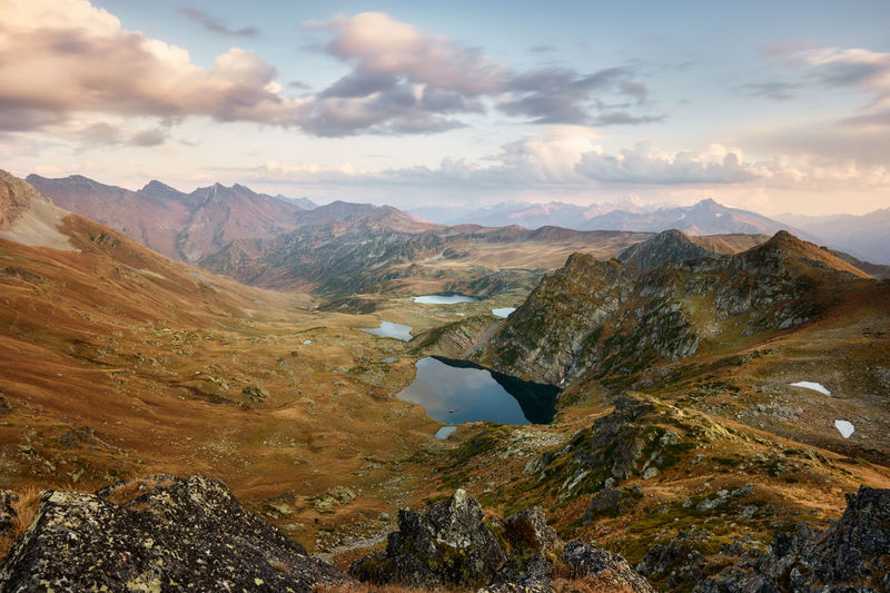 Mountains at sunset, gold alpine field, lakes and mountain ranges, travel and mountain life