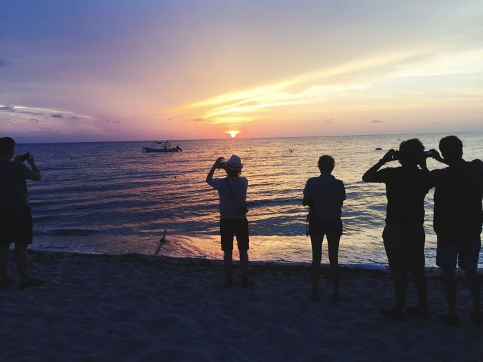 People standing on shore while photographing sunset over horizon