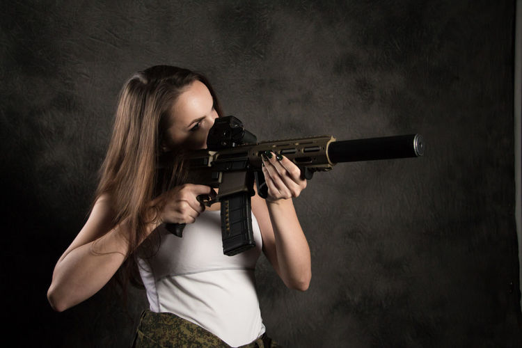 Adult Aggression  Aiming Beautiful Woman Black Background Communication Concentration Gun Hair Hairstyle Handgun Holding Indoors  Long Hair One Person Shooting A Weapon Sign Teenager Warning Sign Weapon Women Young Adult Young Women