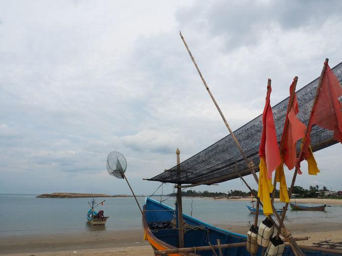Ship moored on beach against sky