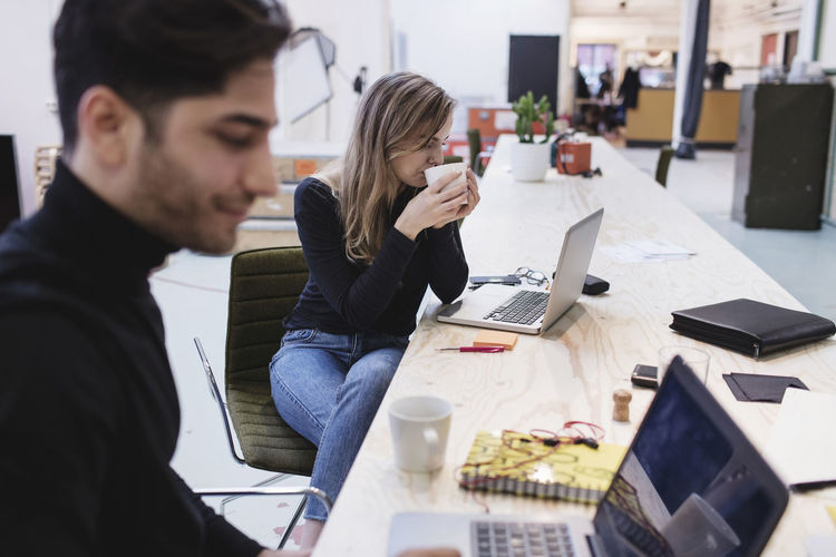 Young woman drinking coffee while sitting with colleague at desk in office