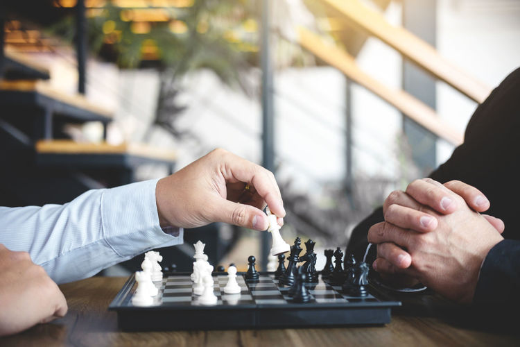 Close-Up Of Business Colleagues Playing Chess In Office