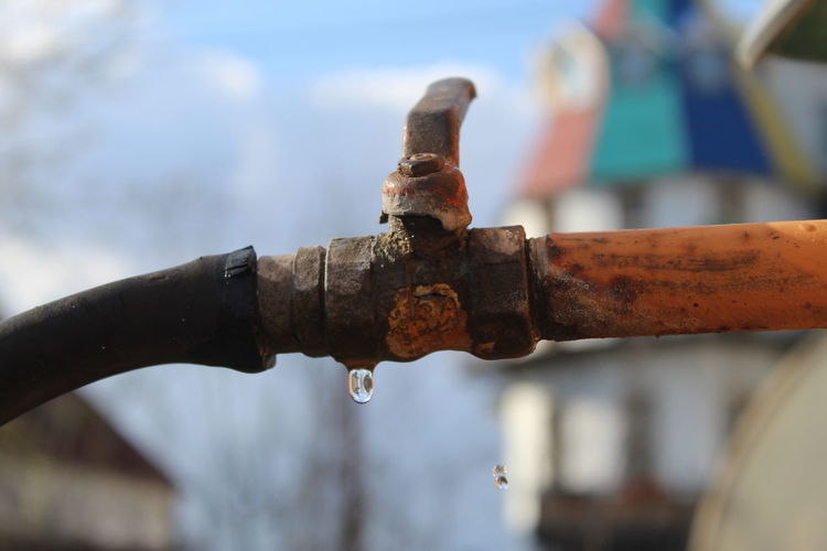 Close-up of water faucet against blurred background