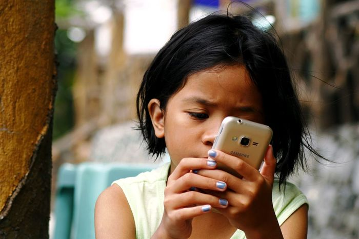 young girl watching movie on a smartphone Cellphone Child Communication Device Electronics  Female Gadget Girl Internet Kid Millenial MOVIE Music Online  Phone Smartphone Surf Technology Telecommunication Video Watch Web Young Youth