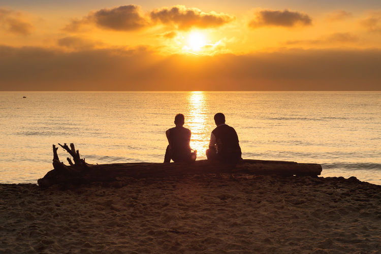 Rear View Of Male Friends Sitting At Beach Against Orange Sky