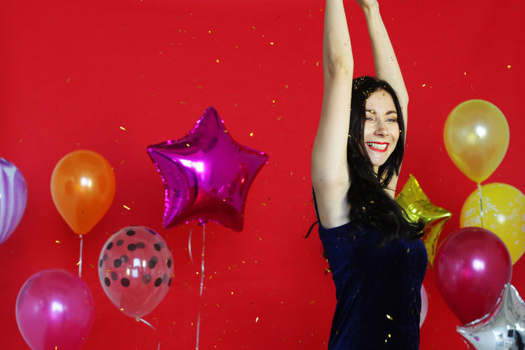 Full frame shot of young woman with red balloons against wall