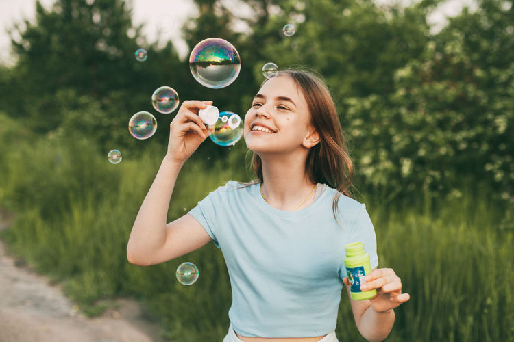 Cute girl making bubble outdoors