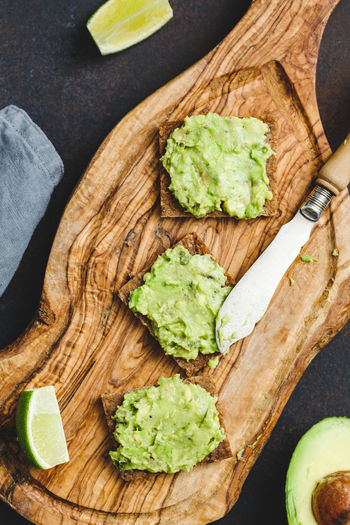 Food And Drink Food Healthy Eating Freshness Wellbeing Fruit Avocado Cutting Board Vegetable High Angle View Bread No People Still Life Table Wood - Material Indoors  Guacamole Knife Directly Above SLICE DIP Table Knife Vegetarian Food