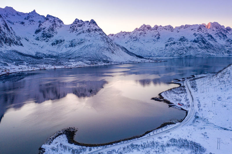 Scenic view of frozen lake and mountains against sky