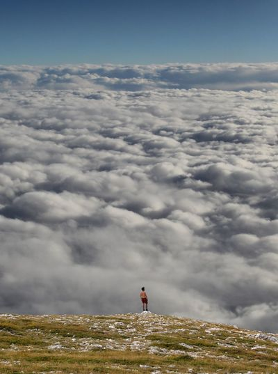 Person Looking At Cloudscape From The Top Of The Mountain