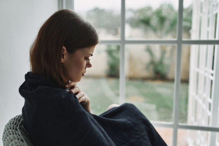 Side view of young woman looking through window at home