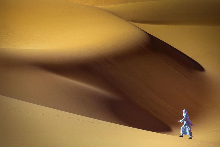 Solitary man walking through sahara desert