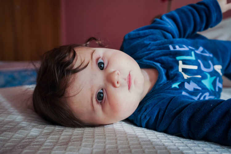 Portrait of cute baby lying on bed at home