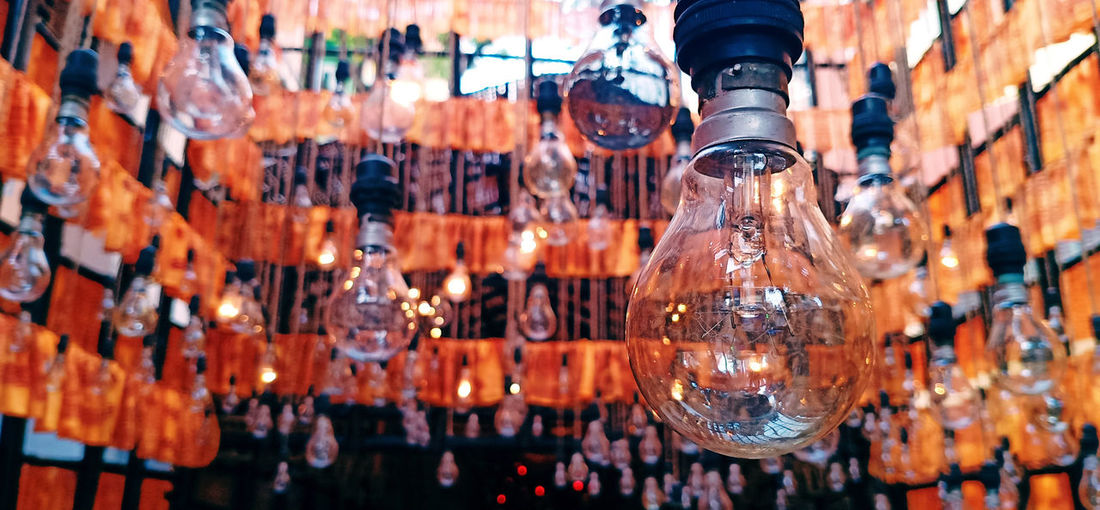 Close-up of glass bottles hanging in row