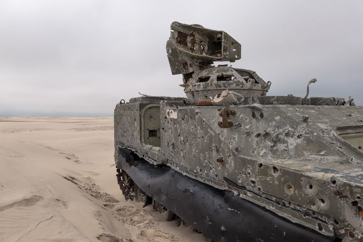 Army tank with bullet holes in the sand