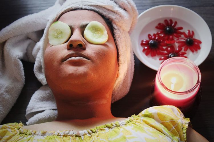 High angle view of woman with facial mask and cucumber slices