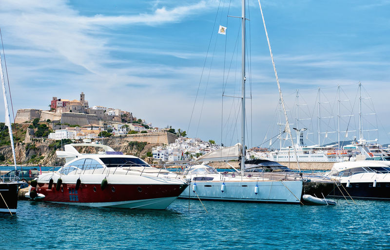 Waterside view to the Dalt Vila old town and moored vessels in the port of Ibiza, Balearic Islands. Spain Castle Eivissa Harbor Ibiza Mediterranean Sea Old Town SPAIN Ancient Architecture Balearic Islands Boats Cloud - Sky Dalt Vila Fortification Fortress Harbor Landmark Landscape Moored Nautical Vessel Outdoors Port Seaport Ship Waterfront Waterside