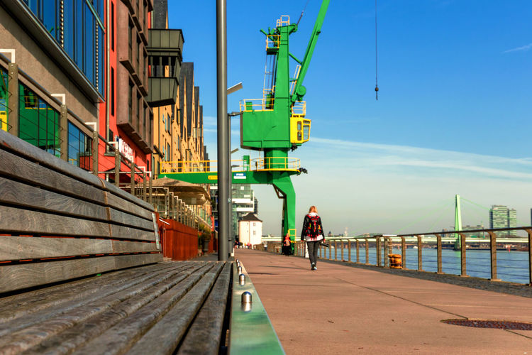 Köln Marcin Adrian Promenade Rhein Architecture Building Exterior Built Structure City Crane Crane - Construction Machinery Day Direction Full Length Incidental People Koeln Lifestyles One Person Pier Railing Real People Rear View Sky Transportation Walking Water