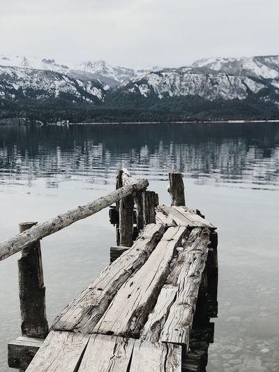 Wooden posts in lake against snowcapped mountains