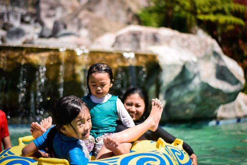 Girls with mother in inflatable ring at water park