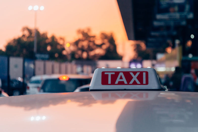 Close-Up Of Taxi Text On Car Roof During Sunset
