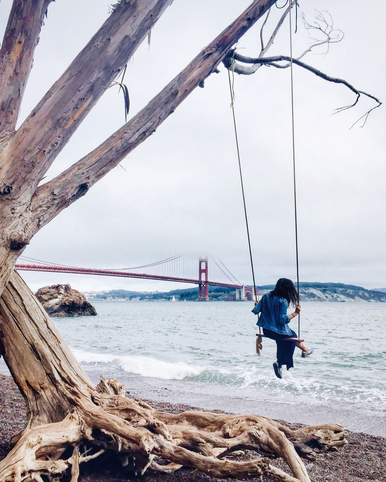 Woman enjoying swing at beach by golden gate bridge against sky