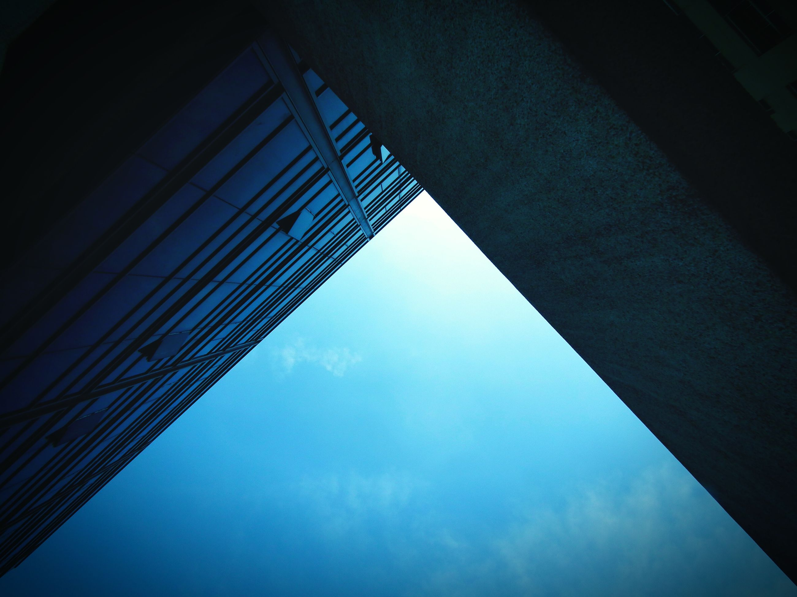 low angle view, architecture, built structure, sky, building exterior, reflection, modern, glass - material, cloud - sky, directly below, building, blue, office building, window, no people, tall - high, cloud, day, city, outdoors