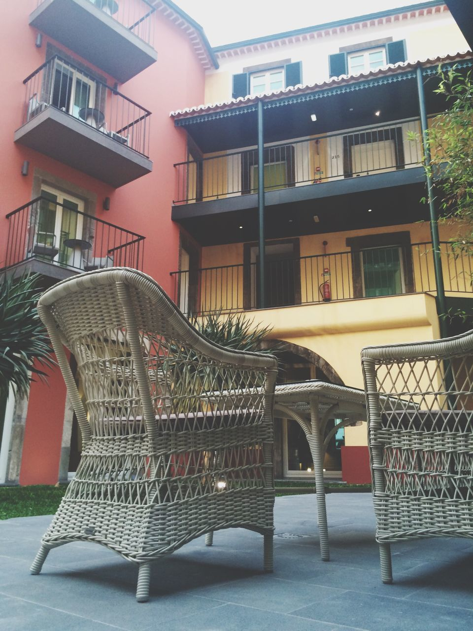 architecture, building exterior, built structure, chair, no people, balcony, outdoors, day