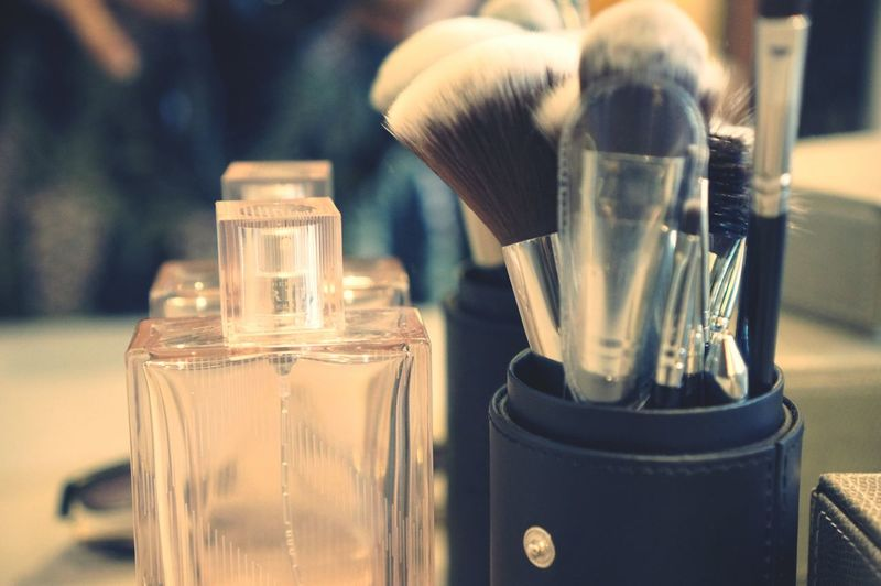 Close-up of make-up brushes by perfume bottle on table
