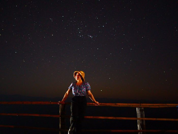 Woman standing on railing against sky at night