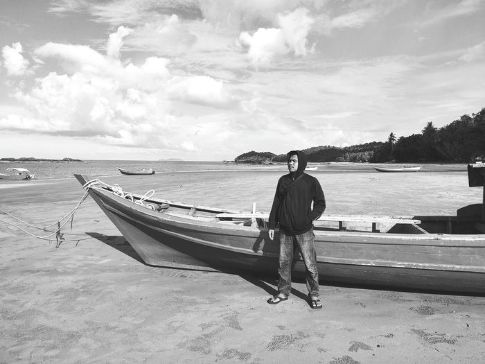 Man standing by moored boat on beach against sky