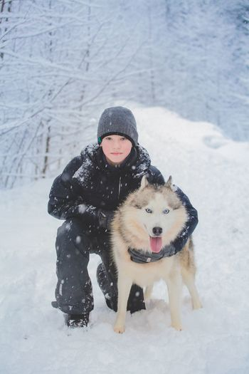 Portrait Of Boy With Dog On Snow Covered Field