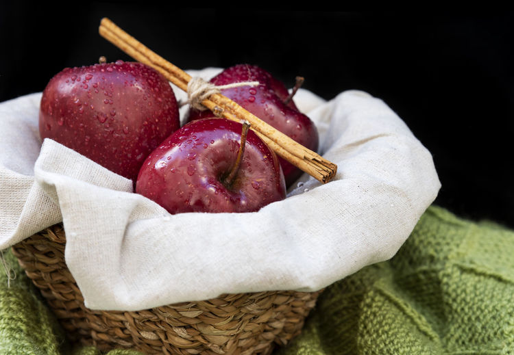 Healthy and organic red apples in a wicker basket and a stick cinnamon on black background with copy space Indoors  Studio Shot Healthy Eating Fruit Close-up Freshness Red Black Background Apple Red Organic Healthy Wicker Basket Cinnamon Copy Space Background Wallpaper Fresh No People Rustic Summer Diet Tasty Delicious Nutrition Agriculture Drops Water