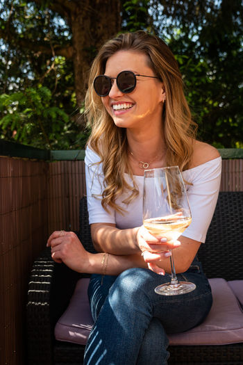 Young woman wearing sunglasses holding drink while sitting on chair