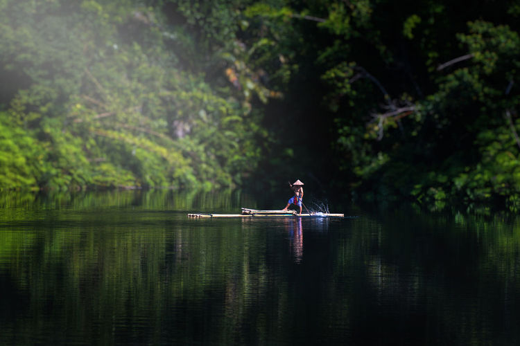 Man in boat on lake against trees