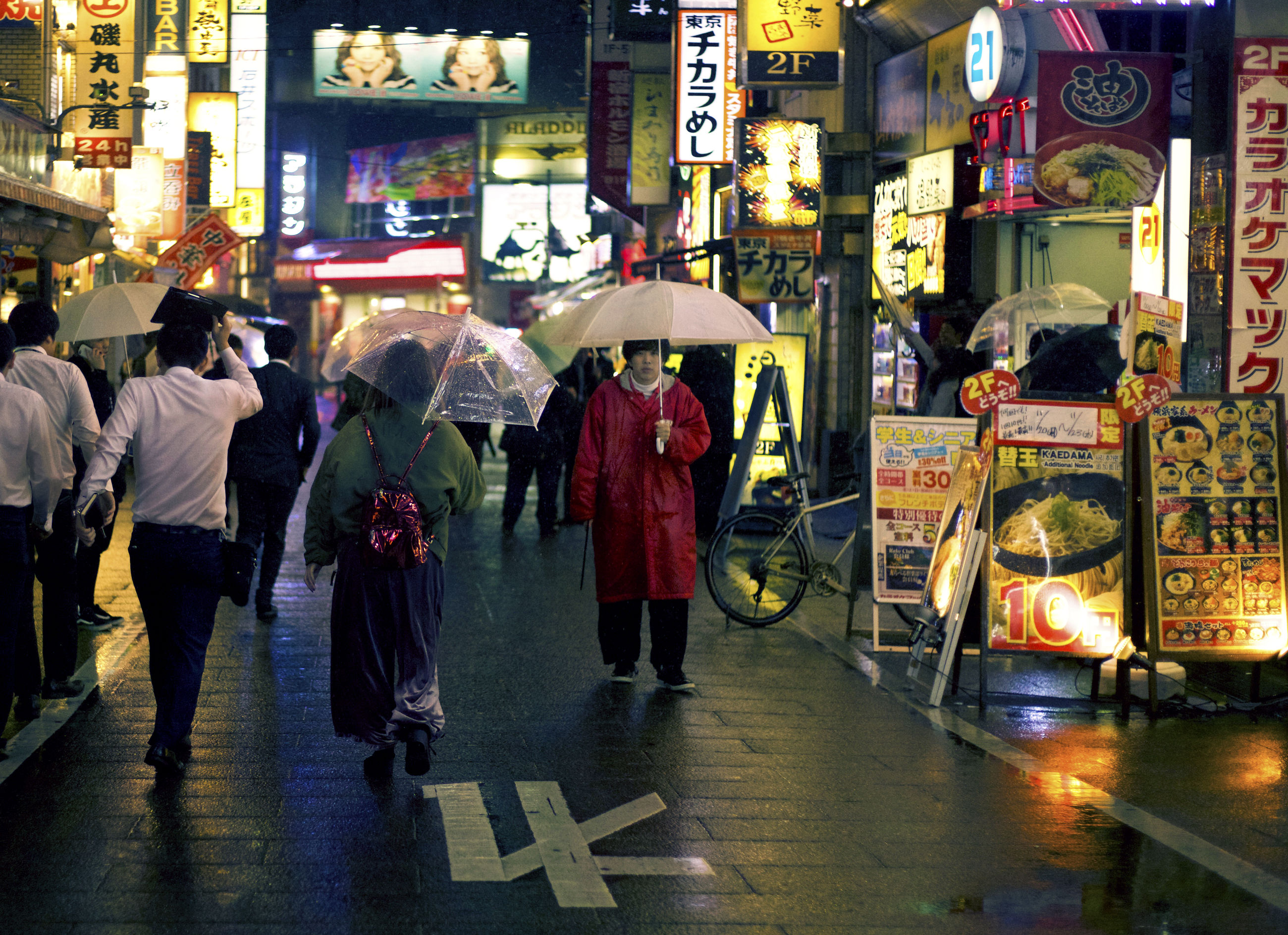 group of people, city, illuminated, city life, real people, architecture, walking, large group of people, street, night, text, crowd, lifestyles, adult, building exterior, transportation, men, women, city street, rain, outdoors