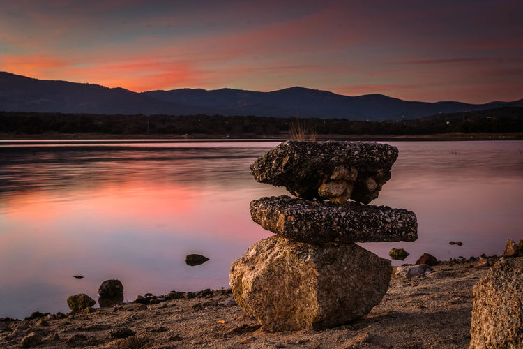 Scenic view of rock stack at lake against sky during sunset